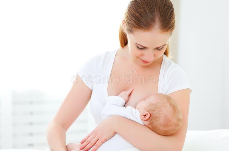 母亲在白色床上的哺乳新出生的婴孩 免版税库存照片
