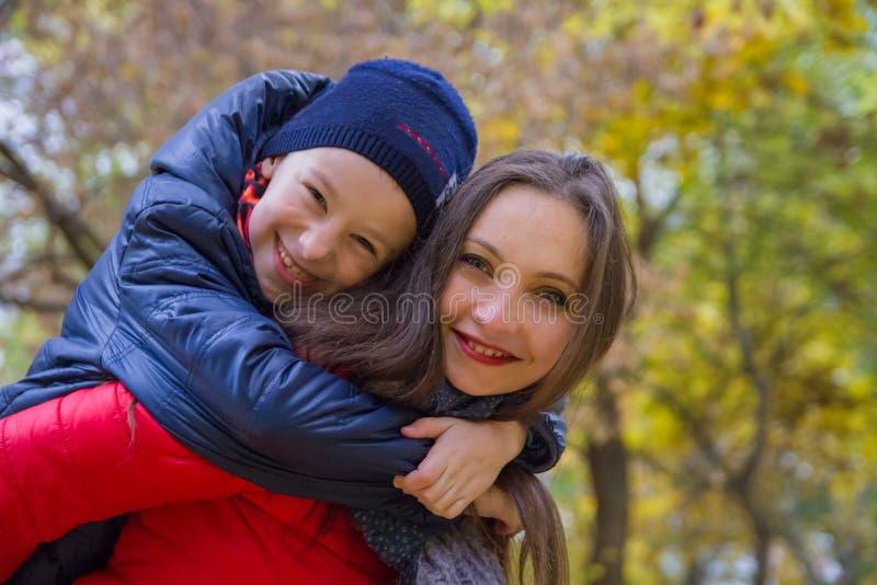 母亲在秋天的给儿子肩扛乘驾 库存图片