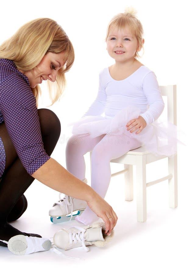 母亲在腿花样滑冰上把她的女儿放 免版税库存照片