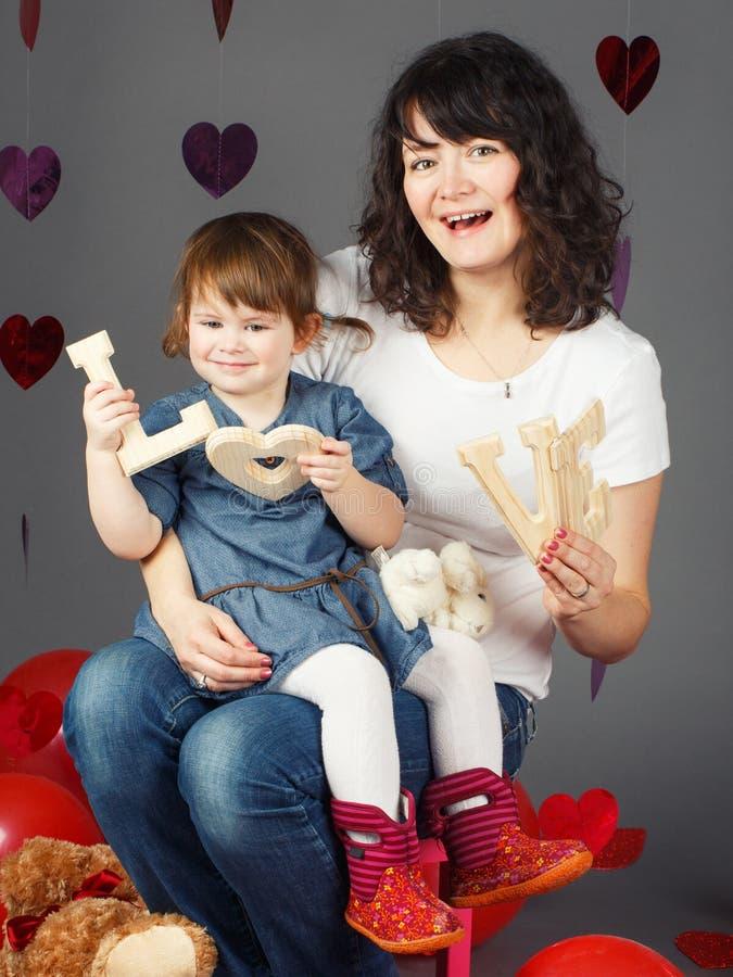 母亲坐与女婴小孩的椅子她的膝部膝盖在拿着木信件的演播室爱微笑的笑 免版税图库摄影