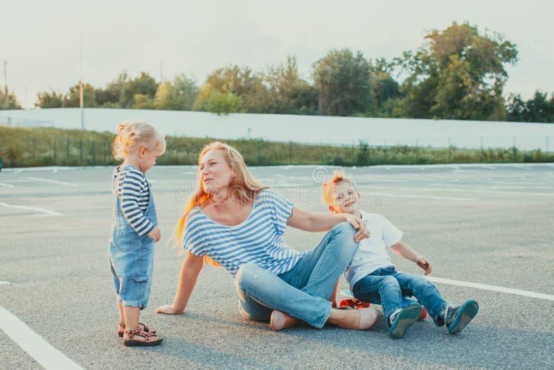 母亲坐与她的女儿和儿子的地面 库存照片