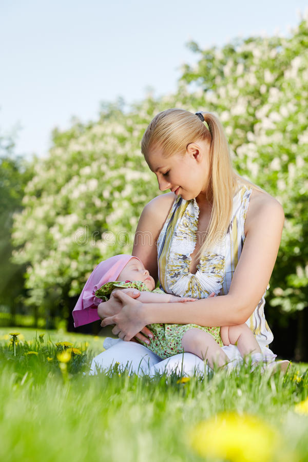 年轻母亲在公园坐并且拿着睡觉的婴孩女孩 库存照片