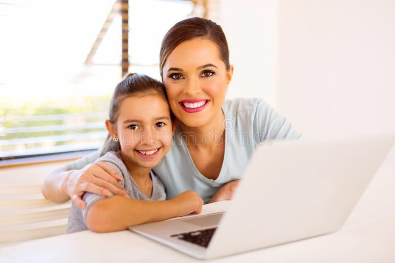 年轻母亲女儿膝上型计算机 免版税图库摄影