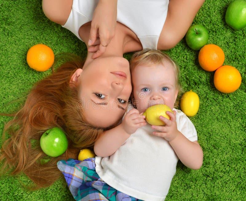 年轻母亲妇女和女儿儿童婴孩哄骗躺下的女孩 免版税图库摄影