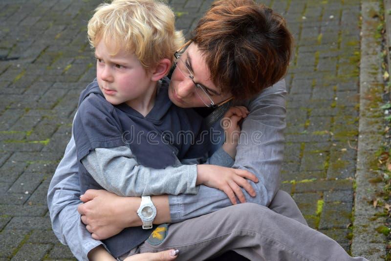 母亲安慰她的孩子 免版税库存图片
