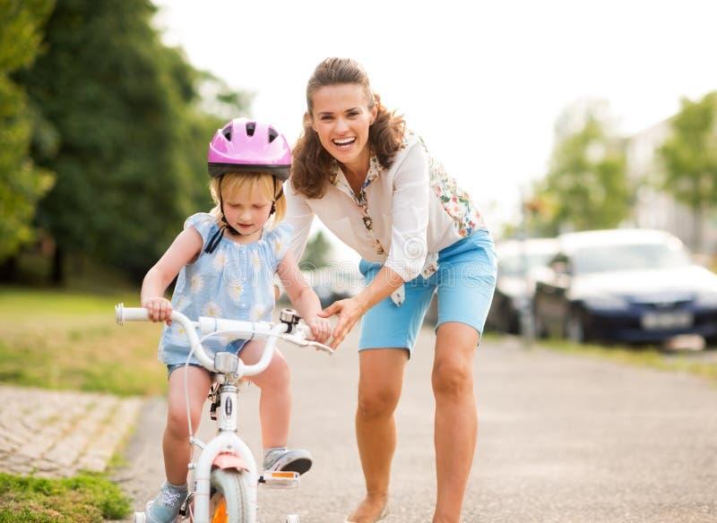 母亲帮助她的女儿学会骑自行车 免版税库存照片