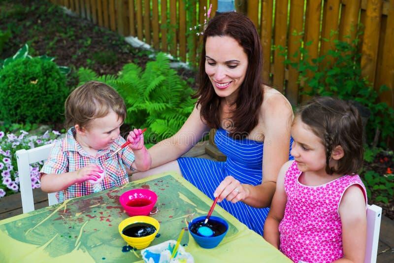 母亲帮助她的洗染复活节彩蛋的孩子 库存照片