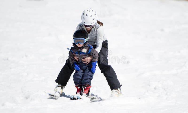 母亲帮助小孩男孩滑雪下坡 安全地穿戴与盔甲 库存图片