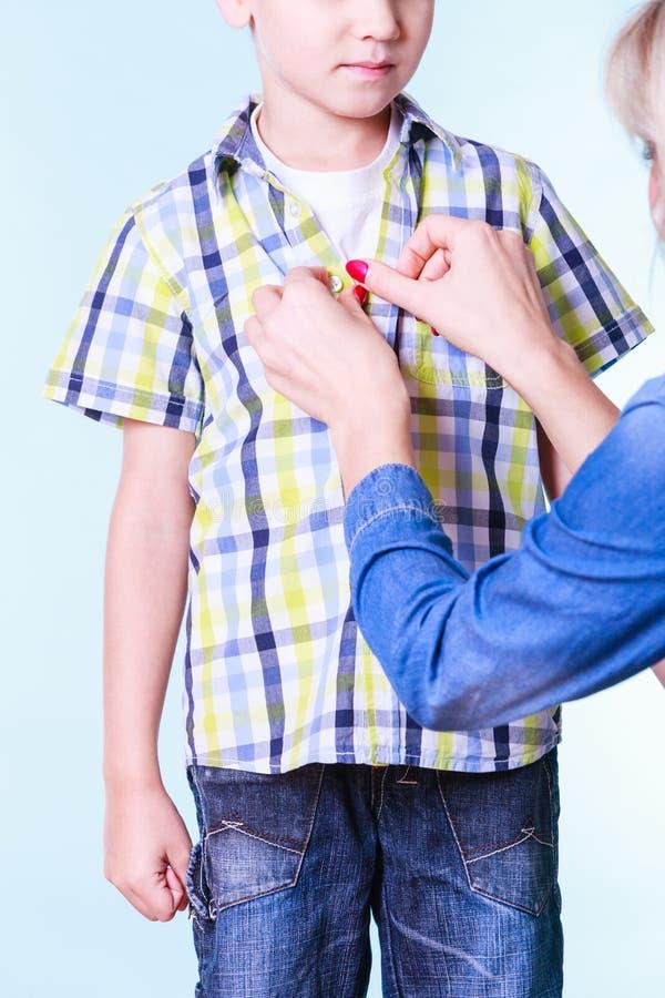 母亲帮助礼服儿子紧固按钮 免版税图库摄影