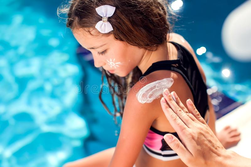 母亲应用太阳在她的女儿皮肤的保护奶油  孩子、夏天、假日和医疗保健概念 免版税库存照片