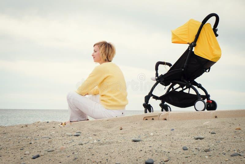 年轻母亲得到一些休息户外 免版税库存图片