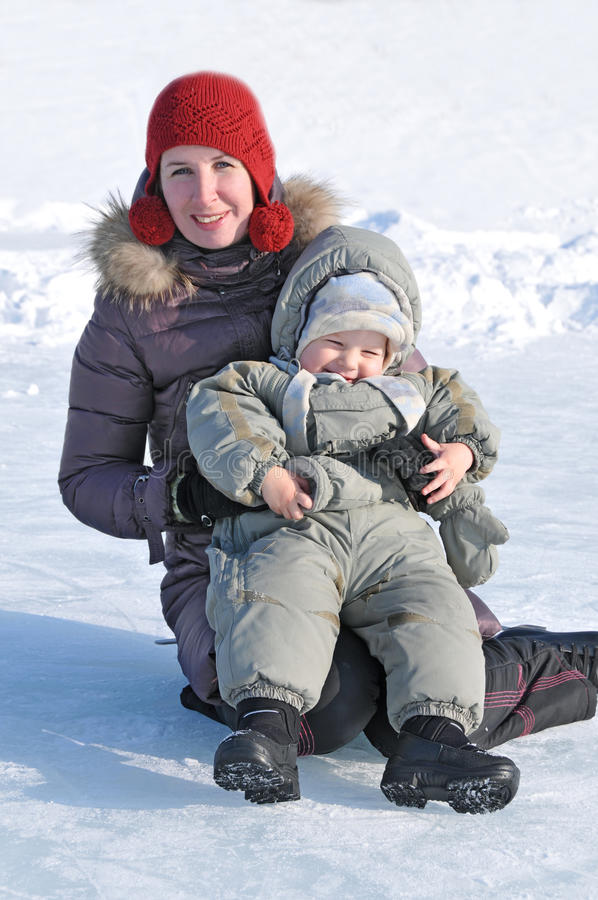 母亲愉快的家庭有使用在冬天公园的婴孩的 免版税库存图片