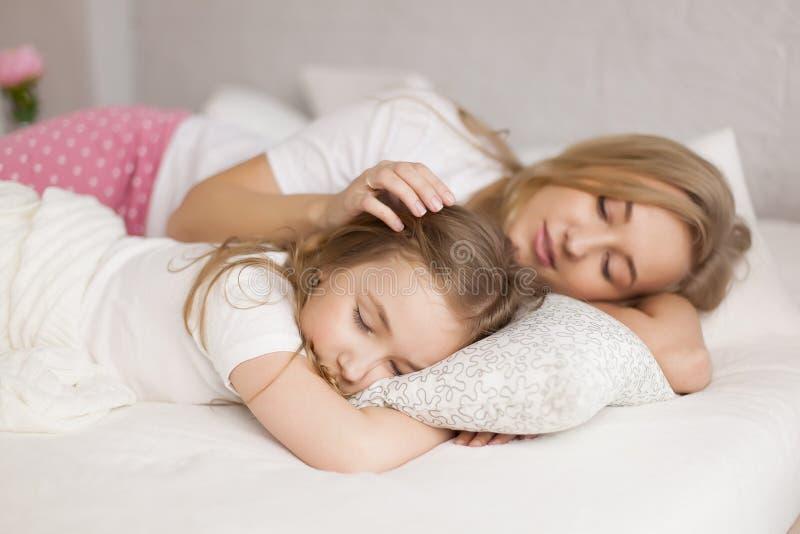 母亲投入她的女儿睡觉 内部 概念关心 免版税库存照片