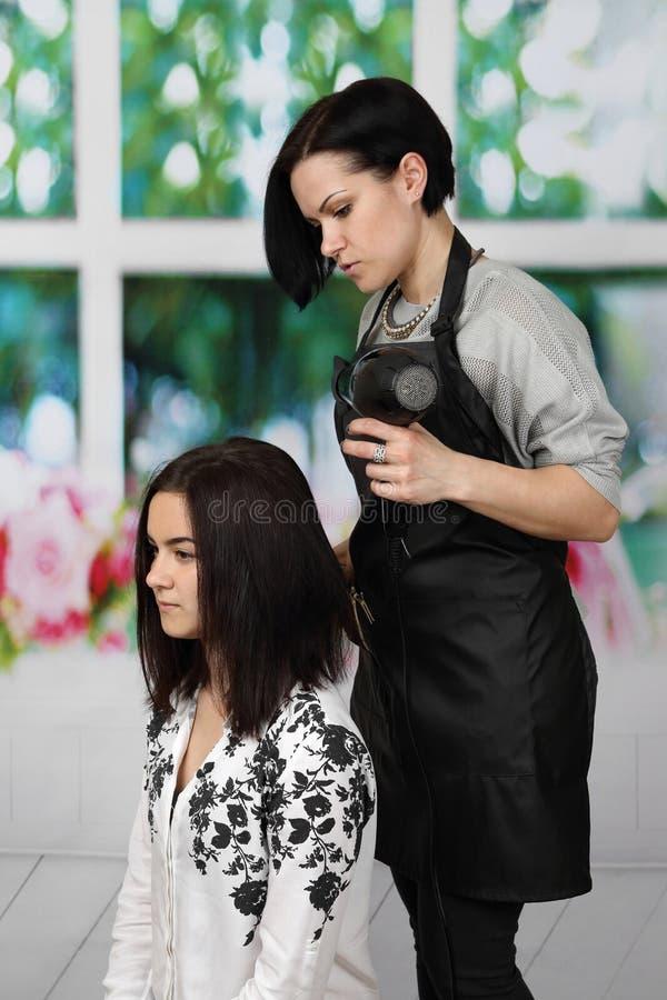 母亲投入她的女儿头发 免版税库存照片