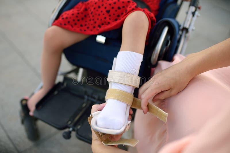 母亲投入整直法她的女儿腿 残疾女孩坐轮椅 儿童大脑麻痹 库存图片