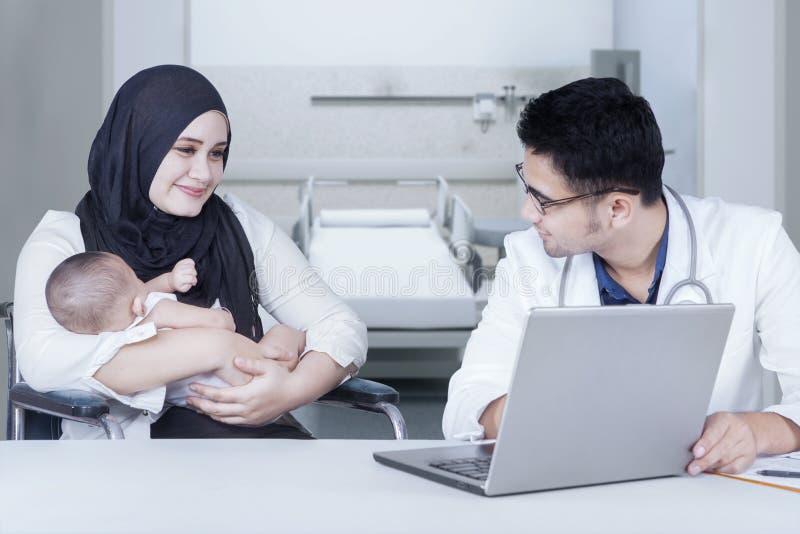 母亲抱着咨询在医生的新出生的婴孩 库存照片