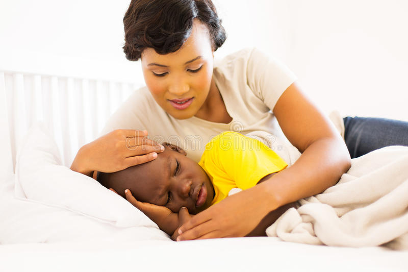 母亲拥抱的病的儿子 免版税库存照片