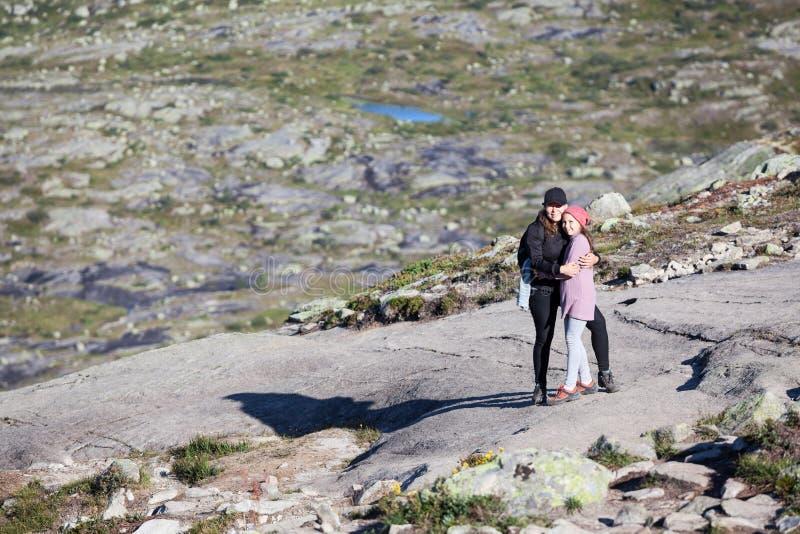 母亲拥抱的青少年的年龄女儿,站立在岩石在远足期间对trolltunga,copyspace ?? 免版税库存图片