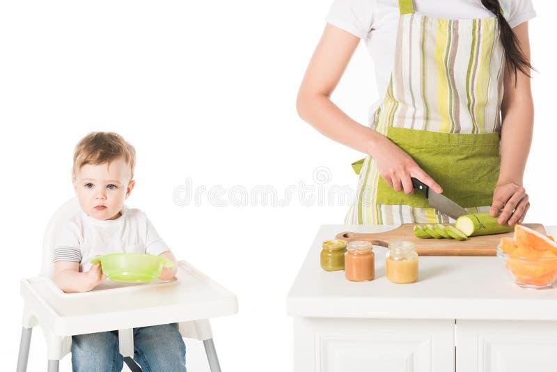 母亲播种的射击围裙坐在有板材的高脚椅子的切口夏南瓜和儿子的 免版税库存图片