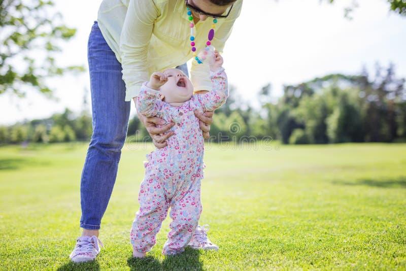 母亲支持的小女儿和帮助她做第一步在绿草在夏天公园 免版税库存照片