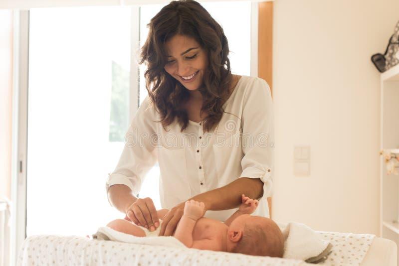 母亲改变的婴孩` s尿布 库存照片