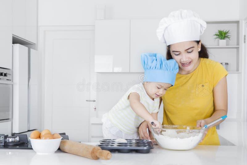 母亲教她的做曲奇饼的孩子 免版税库存图片