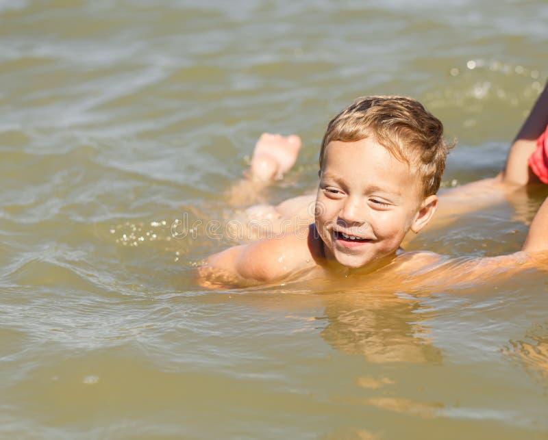 母亲教她的儿子游泳 库存照片