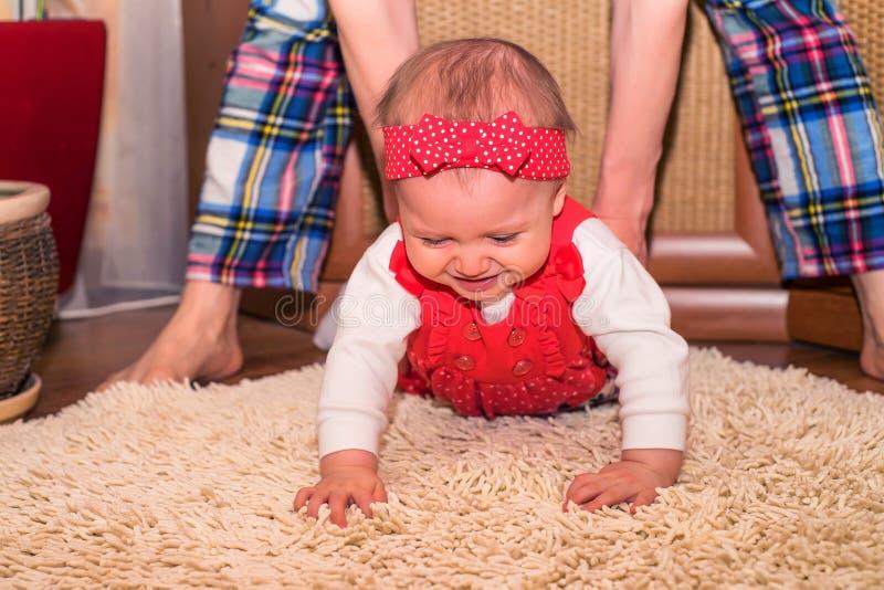 母亲教婴孩对在地板上的爬行 库存图片