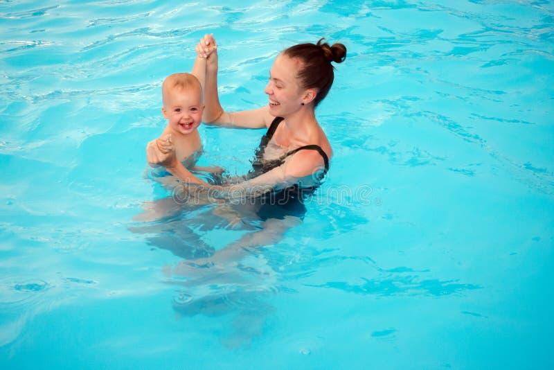 母亲教游泳在水池的一个一岁的孩子 免版税库存图片