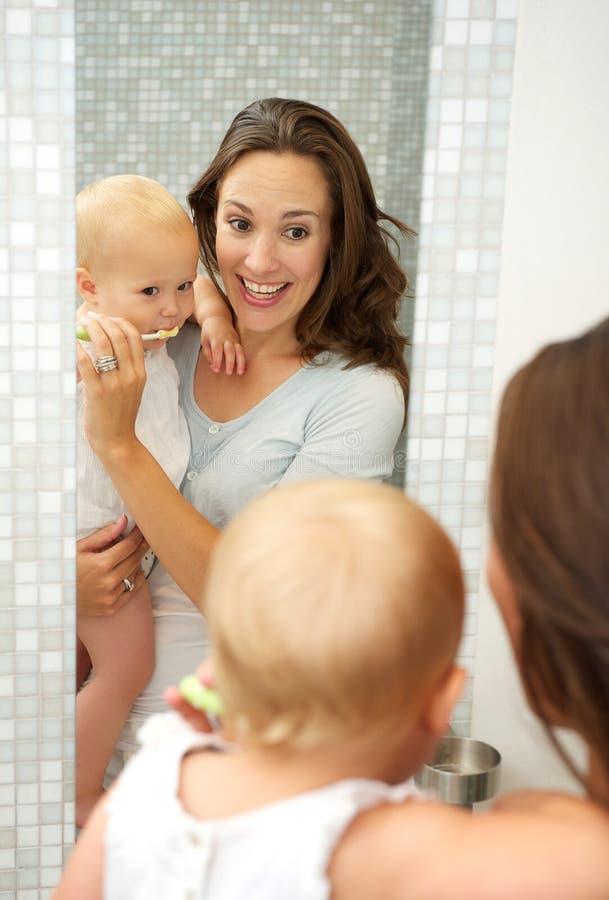年轻母亲教逗人喜爱的婴孩如何刷有牙刷的牙 库存图片