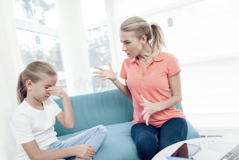 母亲是热情关于研究膝上型计算机 女儿没有从母亲的足够的注意 图库摄影