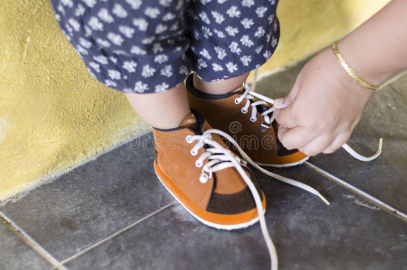 母亲栓她的女儿鞋子 免版税库存照片