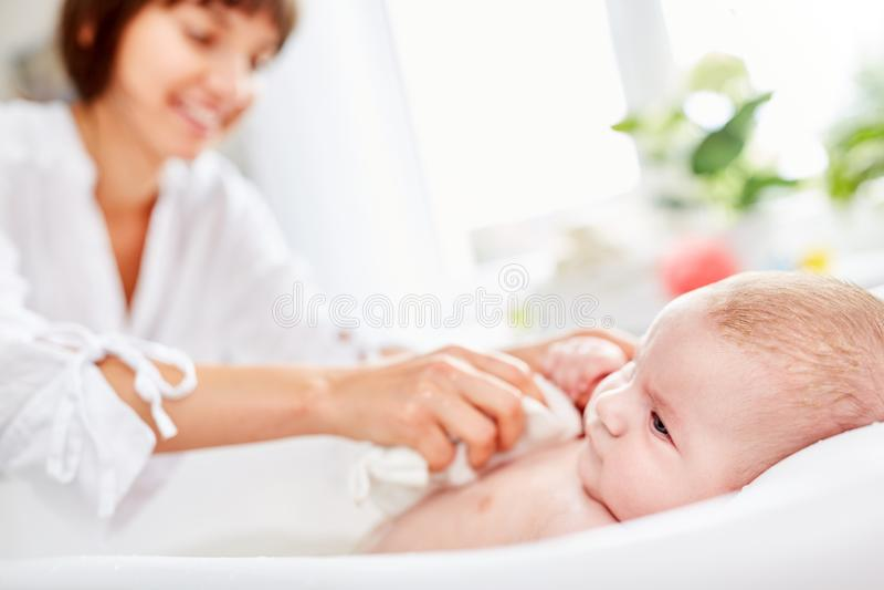 母亲洗涤新出生的婴孩 免版税库存照片