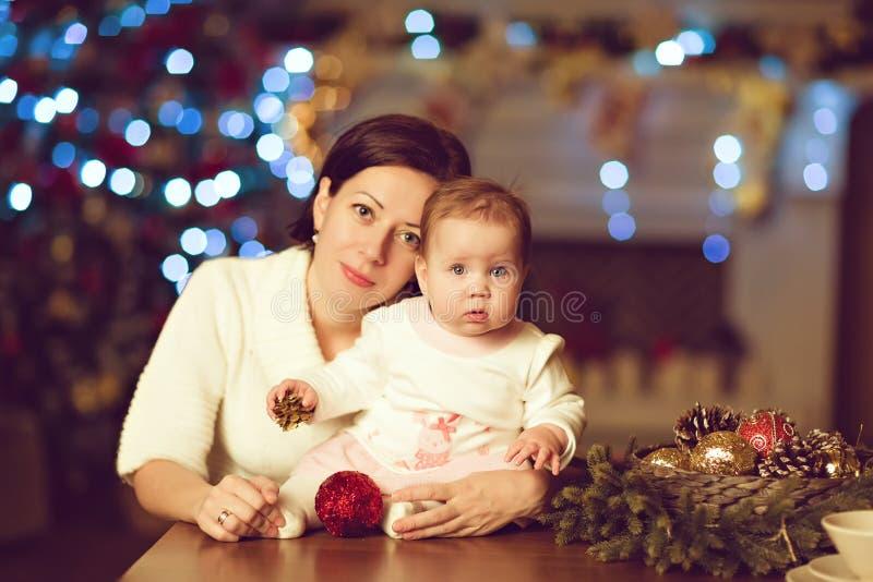 母亲浅黑肤色的男人拥抱白色的小逗人喜爱的胖的女婴 免版税库存图片