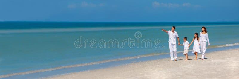 母亲父亲走在海滩全景的儿童家庭 库存照片