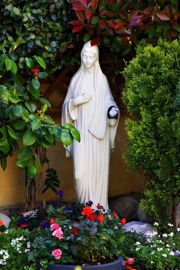 母亲玛丽白色雕象在庭院里 图库摄影