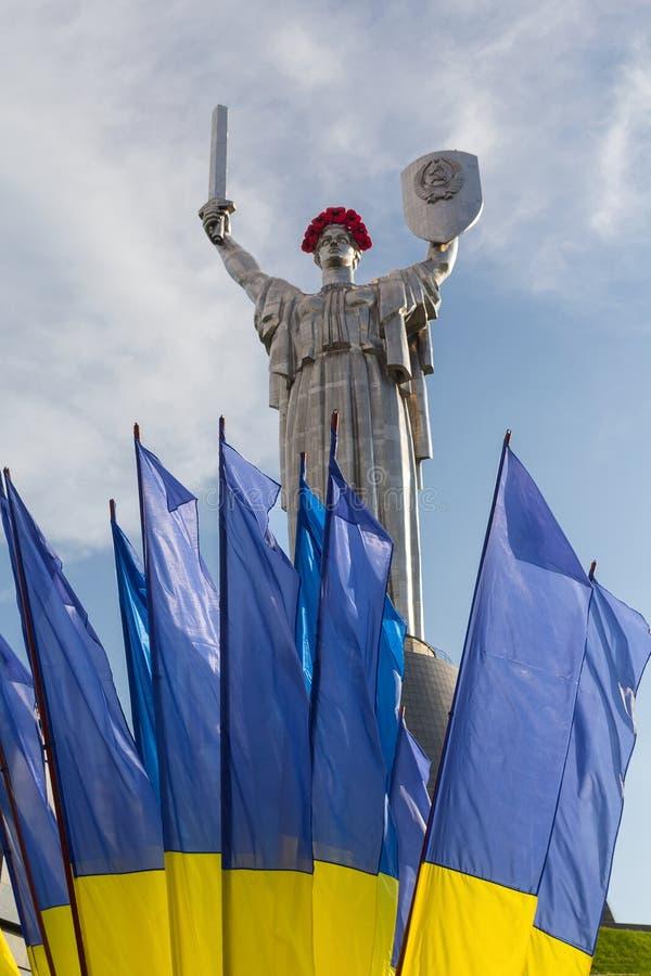 母亲用红色鸦片花花圈装饰的祖国雕象在胜利天在基辅 免版税库存照片
