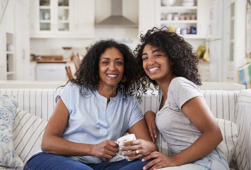 母亲画象与十几岁的女儿坐沙发 免版税库存图片
