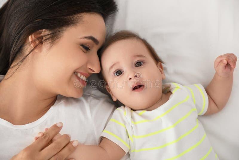 母亲画象有她的说谎在床上的可爱宝贝的 免版税库存照片