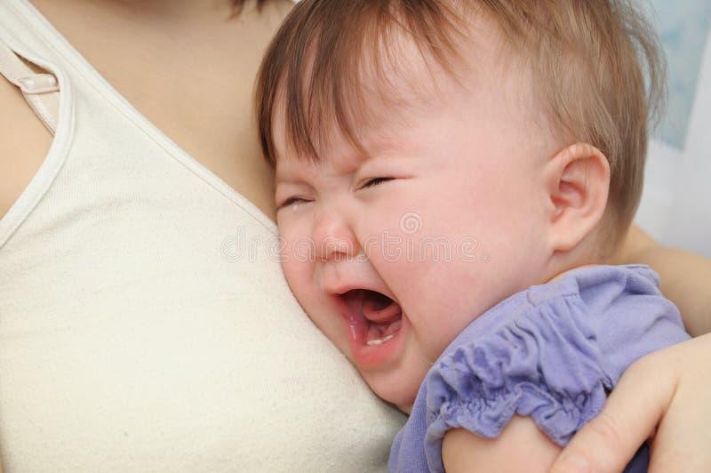 母亲的哭泣的婴孩在手上 拥抱安慰的生气的孩子和镇定 免版税库存图片