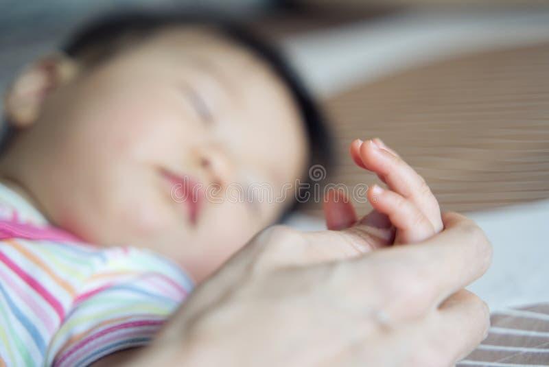 母亲的睡觉在床上的一点年轻逗人喜爱的亚裔婴孩手藏品  在婴孩手指的接近的看法 免版税库存图片