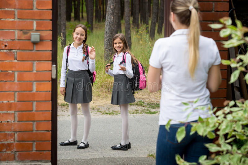 年轻母亲看见她的学校的孩子和挥动对他们 库存照片