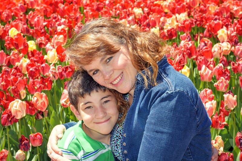 母亲节、妈妈和儿子在郁金香庭院里 免版税图库摄影