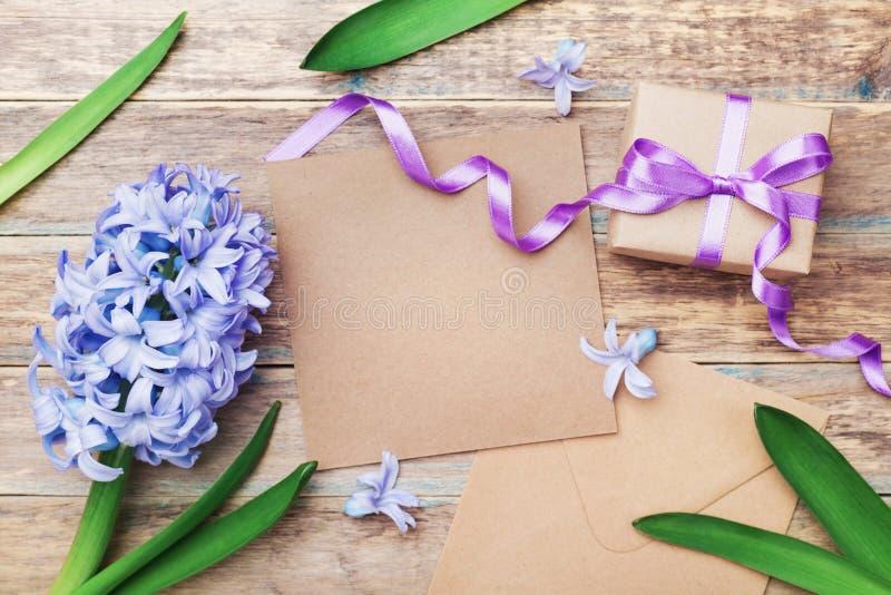 母亲节与卡拉服特信封和礼物或当前箱子的贺卡装饰了在木葡萄酒背景的花 顶视图 免版税库存照片