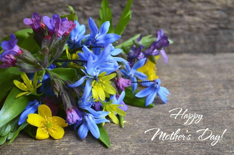 母亲节快乐与第一朵春天花花束的贺卡在老木桌上的 春天假日概念 库存图片