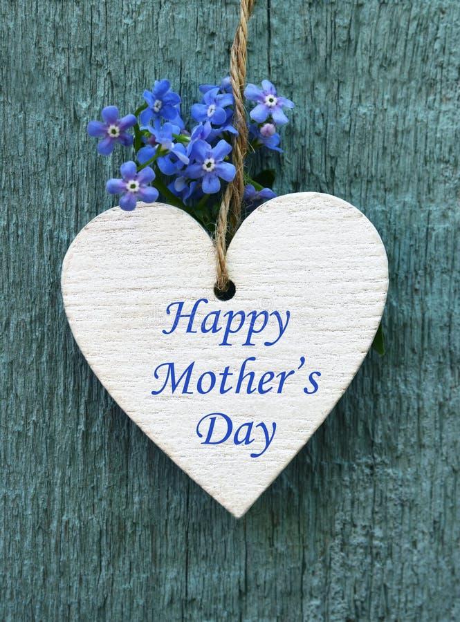 母亲节快乐与装饰白色心脏和勿忘草花的贺卡在老蓝色木背景 图库摄影