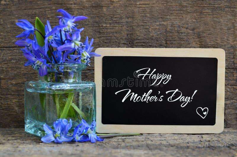 母亲节快乐与Scilla siberica蓝色春天花的贺卡在玻璃花瓶和黑板有文本的在老木b 免版税图库摄影