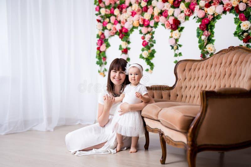 母亲节概念-愉快的美丽的摆在演播室的母亲和她的小女儿 图库摄影