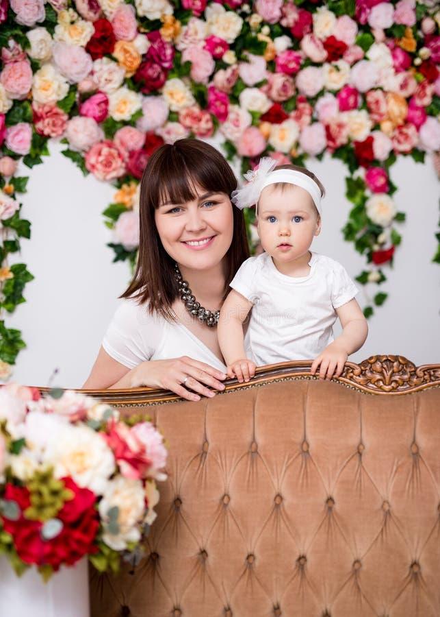 母亲节概念-愉快的美丽的母亲和她的小女儿在花背景 免版税图库摄影