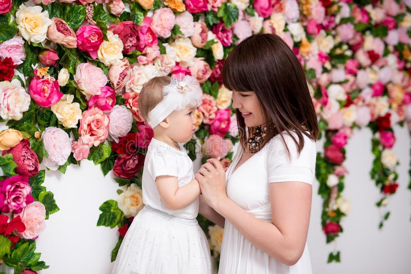 母亲节概念-有一点女儿的愉快的美丽的母亲在花墙壁 免版税库存图片